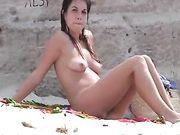 Nudist vrouw op het strand is gefilmd voyeur