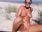 Een geil meisje masturbeert op het strand
